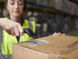 Woman using barcode reader on a box in a warehouse, detail