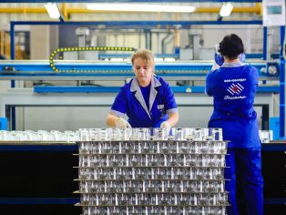 Two women working in glass recycling factory